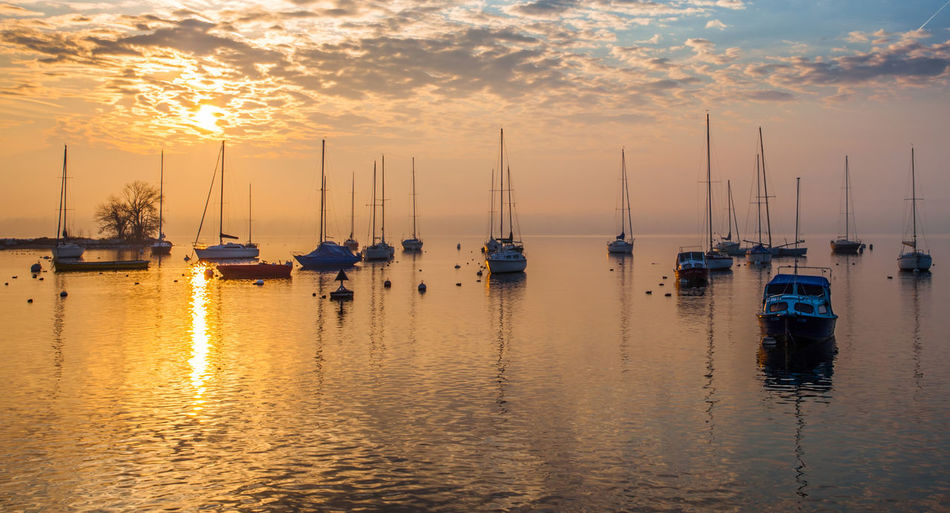 Boats moored in lake geneva against sky during sunset