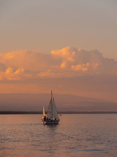 Sailboat Sailing On Sea Against Sky During Sunset