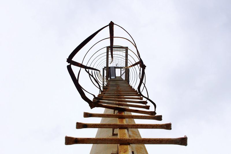 Low Angle View Of Rusty Ladder On Pole Against Sky