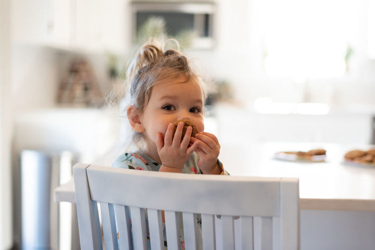 Portrait of cute girl eating at home