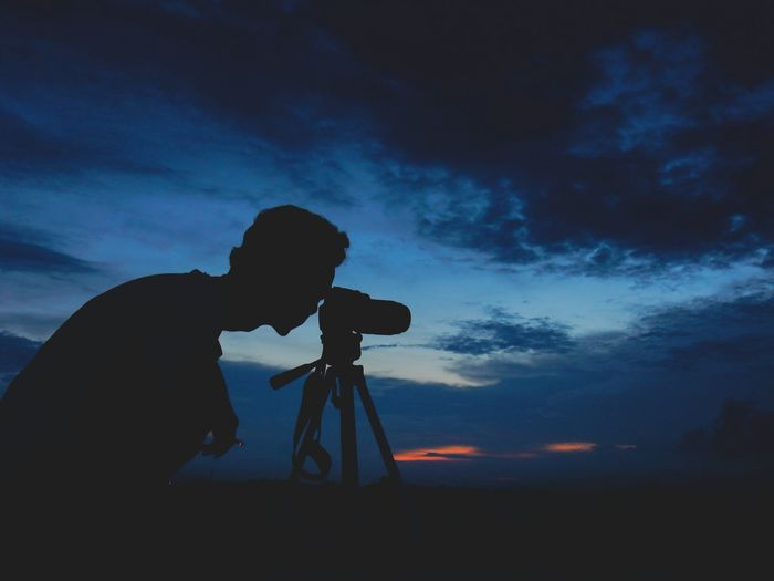 Silhouette of man taking picture of sunset