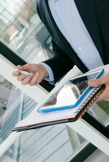 Midsection of businessman holding files and digital tablet in office