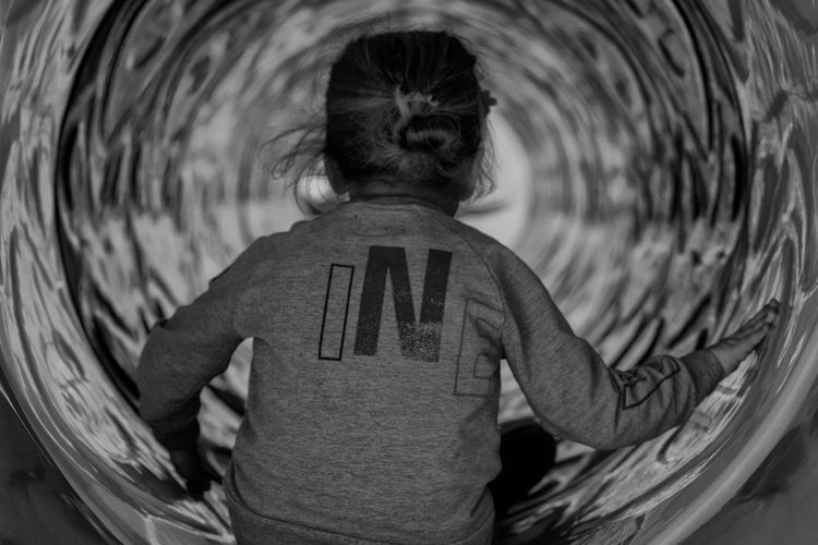 Rear view of girl sitting at play equipment