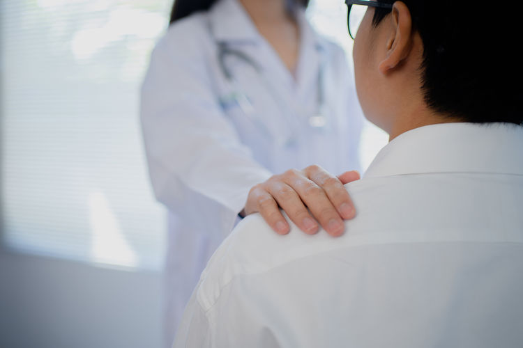 Midsection of doctor explaining patient in hospital