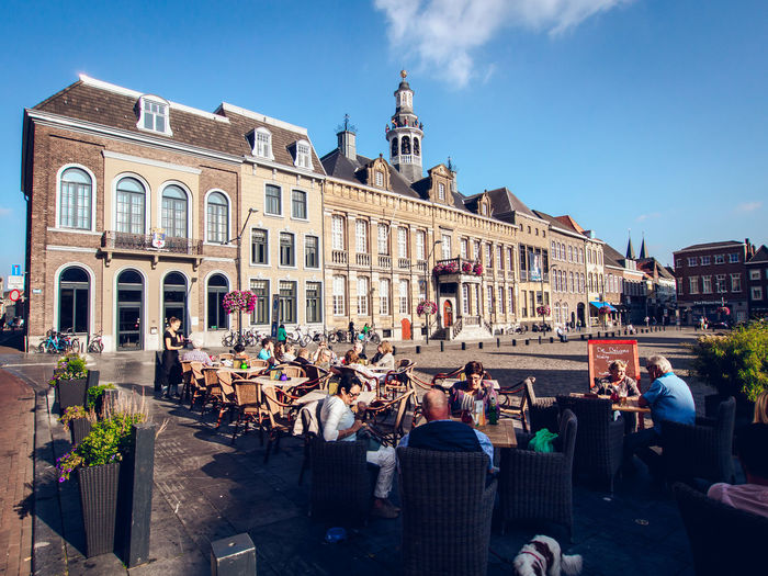 People at town square against blue sky
