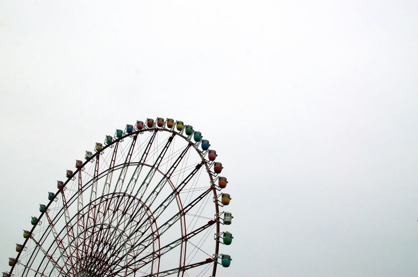 Low angle shot of a Ferris wheel again a flat overcast sky Amusement Park Ride Amusement Park Ferris Wheel Arts Culture And Entertainment Sky Copy Space Low Angle View Enjoyment Multi Colored Curve Architecture Circular Offcentered No People Physics Spinning Joy Teenage Years Japan Travel Tourism