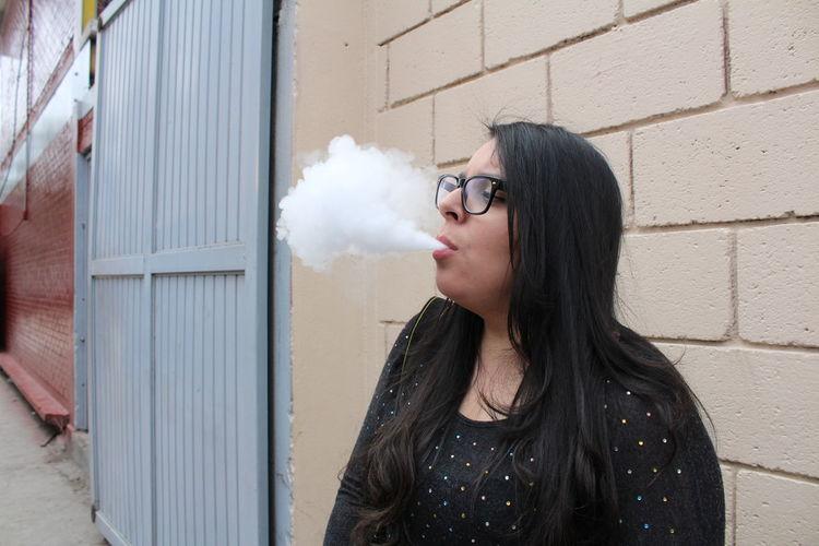 Young Woman Blowing Smoke Outdoors