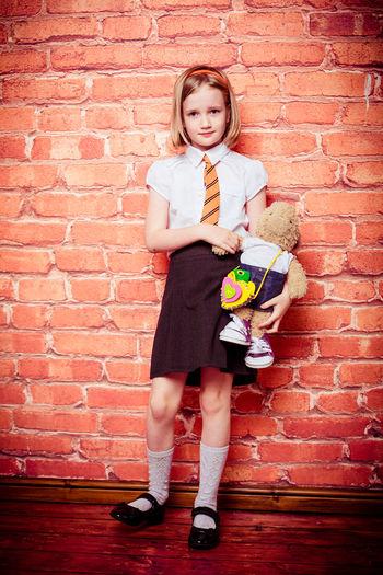 Full length portrait of schoolgirl standing against brick wall