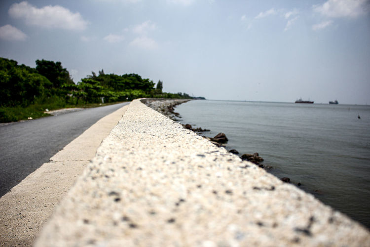 Surface level of road by sea against sky