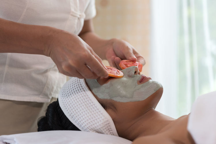 Midsection of beautician adjusting tomato slices on woman eyes during facial mask at spa