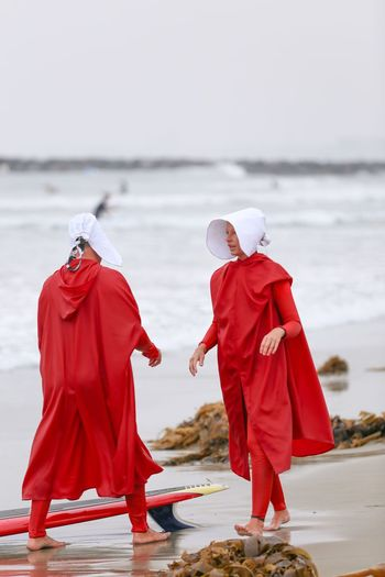 """Blackies Halloween Surf Contest Series • """"Freedom, like everything else, is relative"""" to the size of the wave. -Handmaid's Tale Religion Two People Red Full Length Traditional Clothing Spirituality Real People Water Outdoors Togetherness Women Sea Day Nature Adult Halloween_Collection Halloween Costumes Surfboard Surfing Surf Sand Surfers Costume Handmaid's Tale Halloween 2017"""