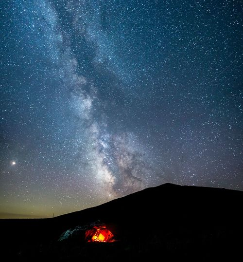 Bonfire on mountain against sky at night