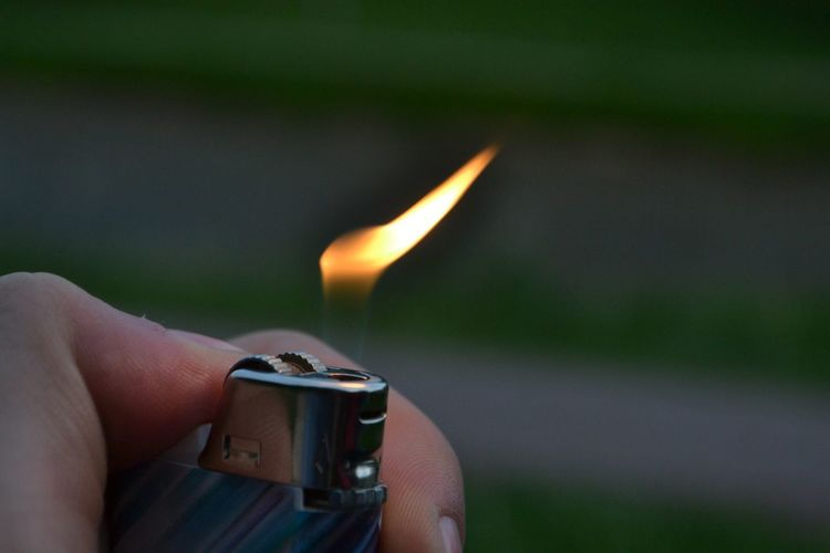 Close-up of hand holding lit cigarette lighter