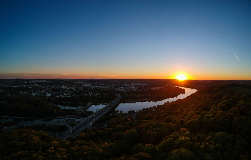 High angle view of river amidst landscape against sky during sunset