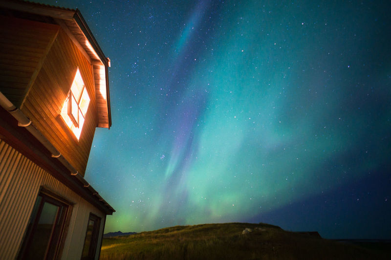 Low angle view house against aurora borealis at night