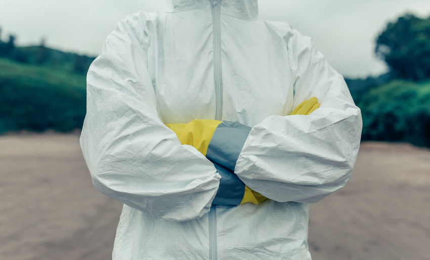 Midsection of doctor wearing protective workwear standing outdoors