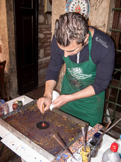 An artist demonstrates Turkish Paper Marbling, Istanbul, Turkey Art Artist Culture Ebru Art Handicraft Heritage Indoors  Istanbul Istanbul City Istanbul Turkey Looking Down Marbling One Person Painting Paper Marbling Preparation  Real People Skill  Souvenir Standing Table Tourism Traditional Art Travel Photography Turk