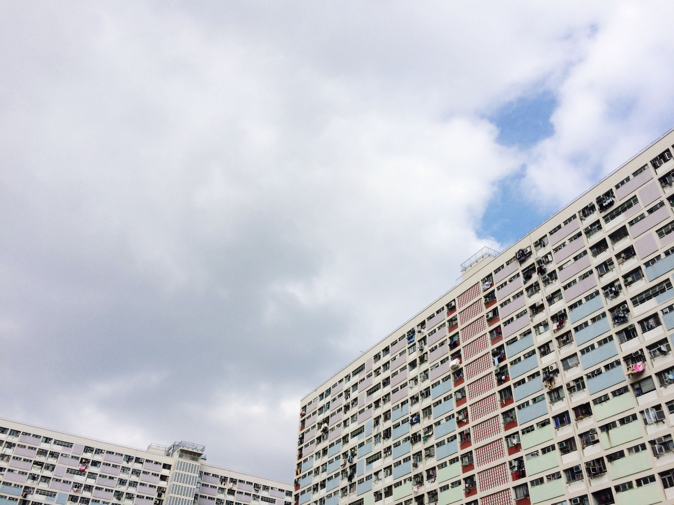 building exterior, architecture, built structure, sky, low angle view, city, cloud - sky, cloudy, building, cloud, modern, office building, residential building, residential structure, overcast, day, skyscraper, outdoors, tall - high, window