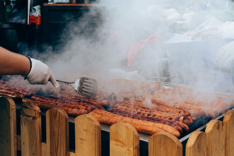 Cropped Image Of Hand Cooking Sausages On Barbecue Grill