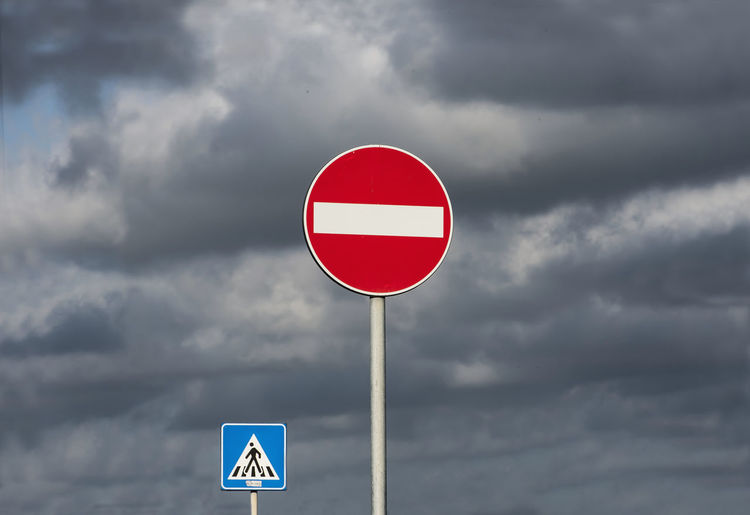 Road signs against cloudy sky