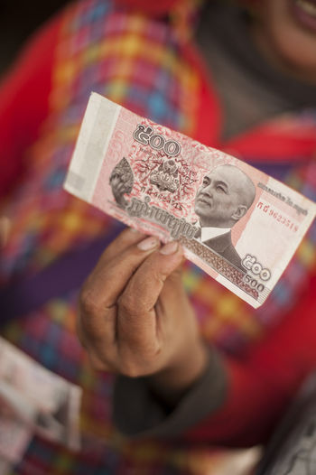 Midsection of woman holding paper currency