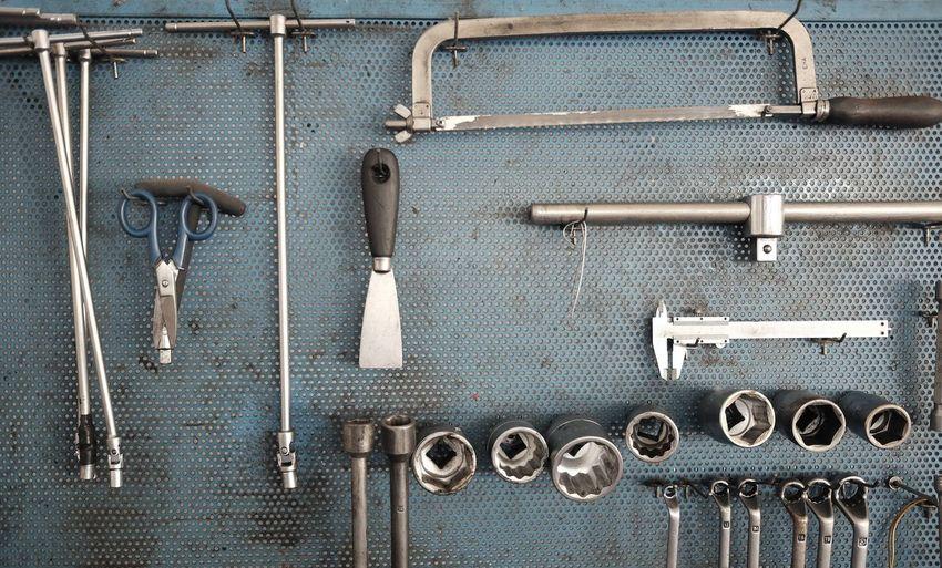 Hand tools hanging on metal in workshop