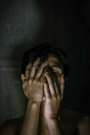 Portrait of a young man covering face
