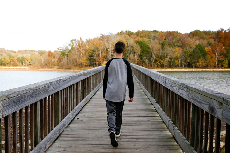 Boy walking across bridge over lake during autumn Child Boy Nature Nature Walk Walking Bridge Bridge - Man Made Structure Autumn Fall Autumn colors Fall Colors State Park  Tennessee Nashville NASHVILLE,TENNESSEE Nashville TN Autumn Trees Autumn Collection Fall Beauty Fall Collection Nature Hike Hike Hiker Hiking Hiking Adventures