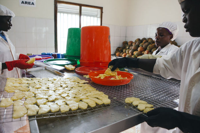 Africa African Dried Fruit Employees Entrepreneur Factory Food Food And Drink Fresh Freshness Fruit Healthy Eating Indoors  People Pineapple Plantation Preparation  Real People SLICE Slices Small Business Social Business Trays Workers Working