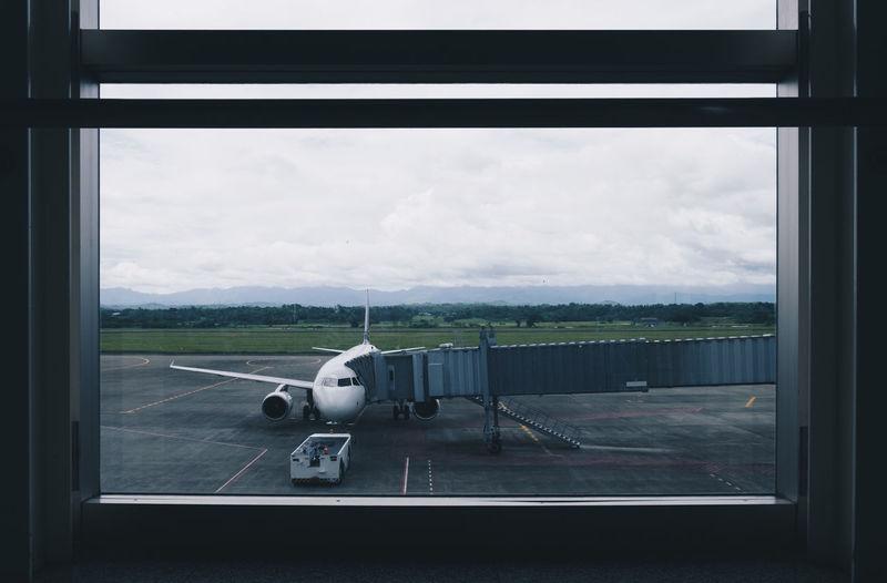 Airplane on runway seen through window