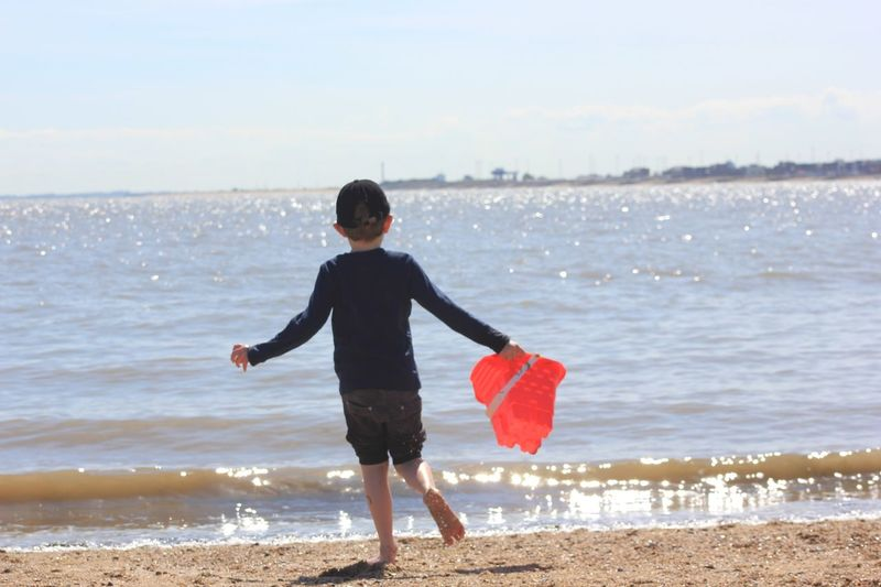 Full length of boy standing on beach against sky