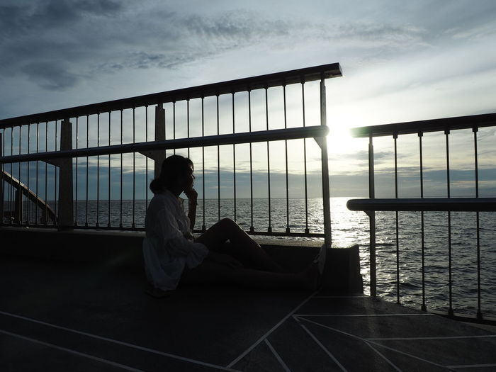 Side view of woman sitting on railing against sea