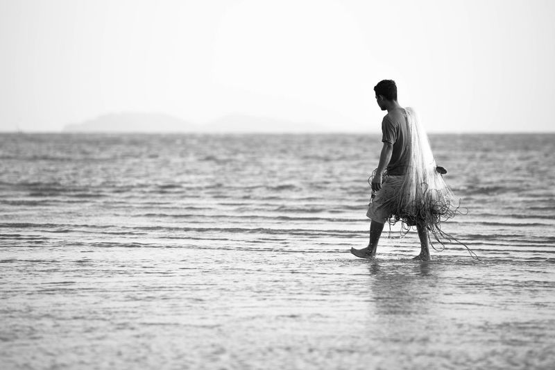 Side View Of Fisherman Carrying Fishing Net And Walking On Wet Beach