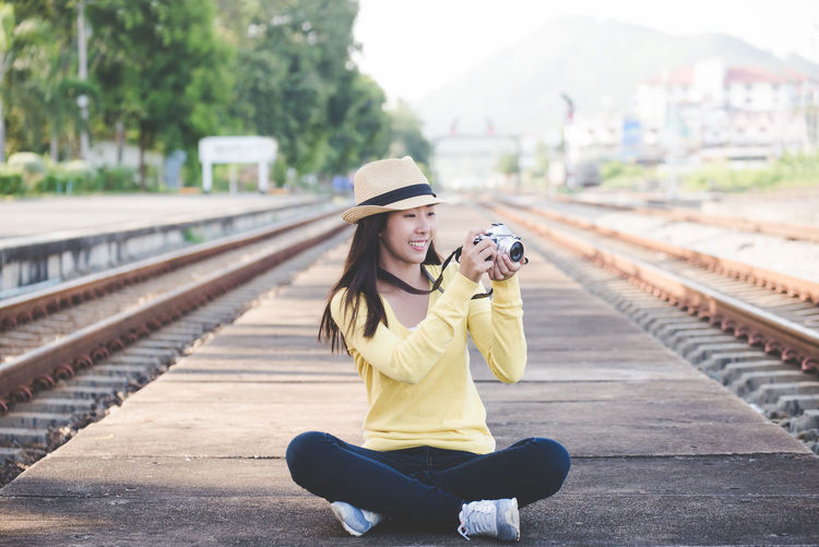 Woman photographing while sitting on railroad track