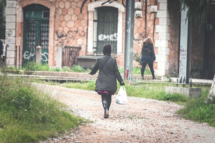 Woman On Street carries her shoppings. Street Photography Urban Exploration In The City Black Coat Nikon