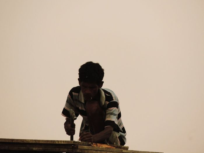 Man couching on roof against sky