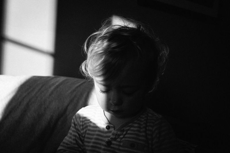 Cute Baby Girl Looking Down While Sitting On Sofa In Darkroom