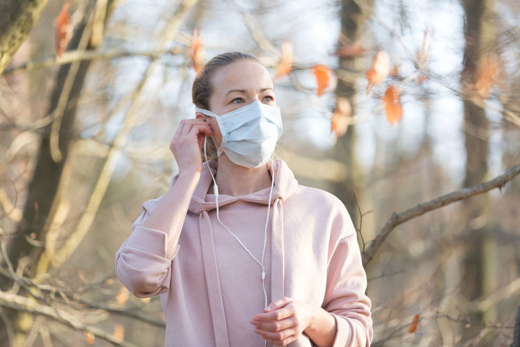 Woman wearing mask standing at park