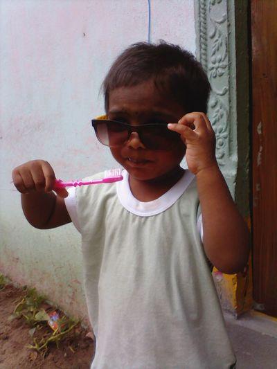 Boy in sunglasses brushing teeth outside door