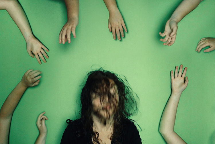 Blurred Motion Of Woman Surrounded By Hands Against Green Background