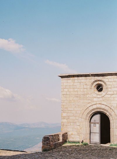 A building with a door open, on top of a mountain in Salamanca, Spain. Arch Architecture Building Building Exterior Built Structure Cloud - Sky Day Film Photography Mountain Top No People Old Outdoors Sky Stone Wall The Past