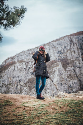 Outdoor portrait of young girl looking at the camera through binoculars One Person Full Length Lifestyles Real People Casual Clothing Leisure Activity Nature Sky Women Adult Plant Standing Rock Solid Rear View Rock - Object Activity Outdoors Jeans Funny Binoculars Girl Mountain Hiking My Best Photo
