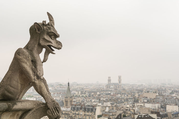 Gargoyle over paris at Notre Dame on an overcast day Architecture Attraction Cathedral Catholic Chimera Church Cityscape Demon Devil Famous Place Gargoyle Gothic Landmark Medieval Monster Monument Myth Notre Dame De Paris Overcast Religion Scary Sculpture Skyline Statue Travel Destinations