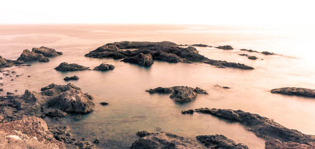 Rocks On Sea Shore Against Sky During Sunset