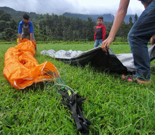 Kids help paragliders fold the parachute. For money of course😂 Paragliding Parachute Paraglider Paragliding Fun Child Worker Kids Working Men Grass Green Color Outdoors Adventure Explore ExploreEverything Leisure Activity Go Explore Exploration Real People at Puncak  Bogor