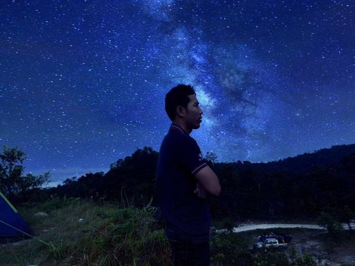 Side view of man standing against star field at night