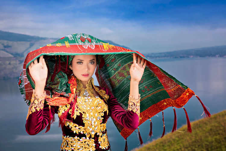 Portrait of woman in traditional clothing standing against lake and sky