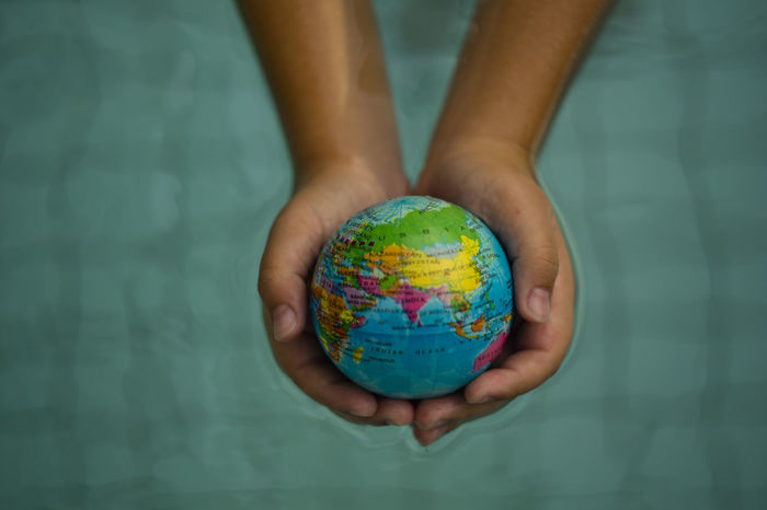 Above close up looking down on hands holding the world over water ASIA Asia Pacific Check This Out Hand Holding Hands Map Plant Power Cat Citizen Of The World Citizenship Continent Ecology Energy Ethnic Indoors  Ocean Planet Protection Refugees Sustainability Sustainable Sustainable Resources Water World