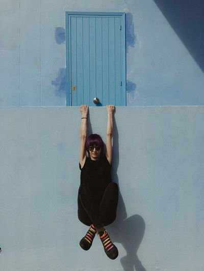 Full length of woman hanging on retaining wall