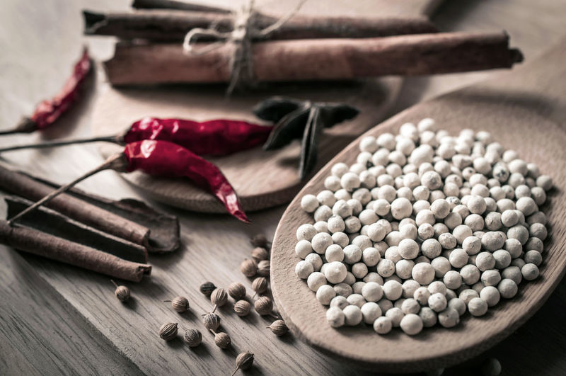 High angle view of white peppercorns with spices on cutting board